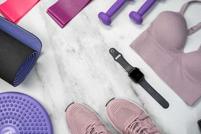 Apple Watch und Fitness-Ausrüstung auf Boden liegend