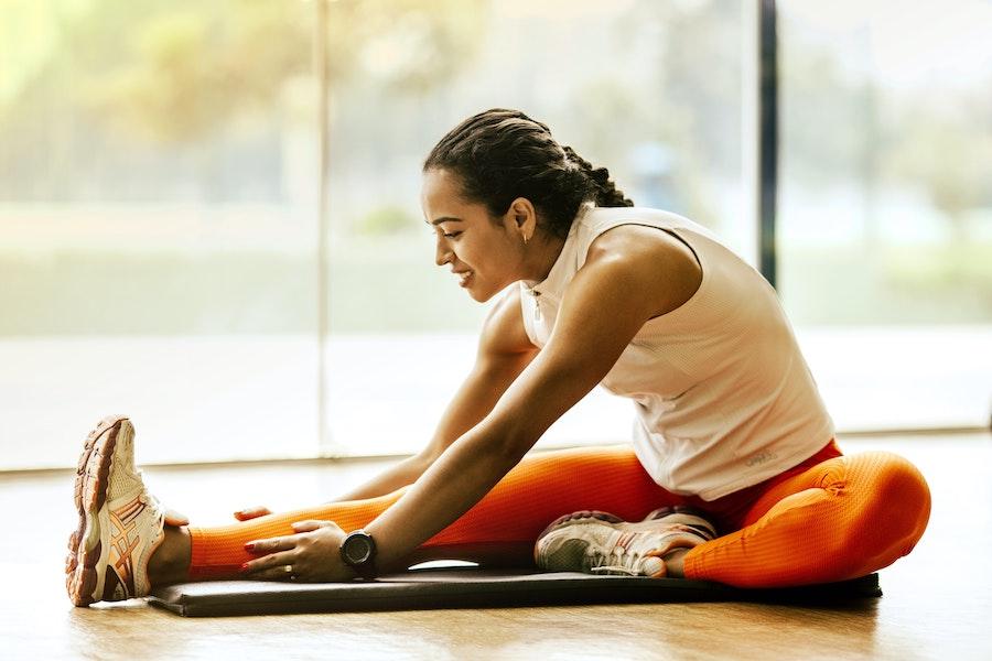 Frau mach Dehnübungen auf Fitnessmatte