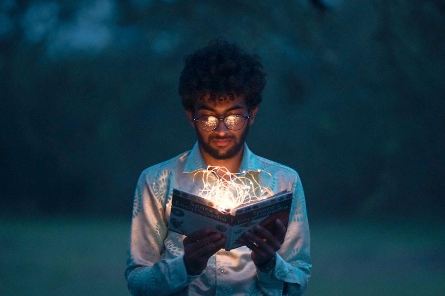 Mann schaut in ein leuchtendes Buch