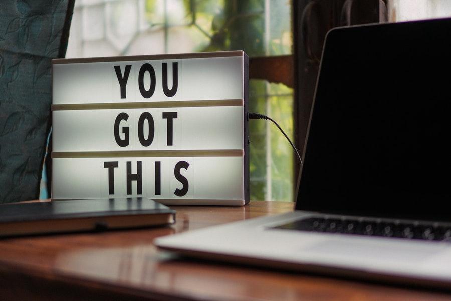 """Schreibtisch mit Laptop und kleiner Textanzeige """"You Got This"""""""