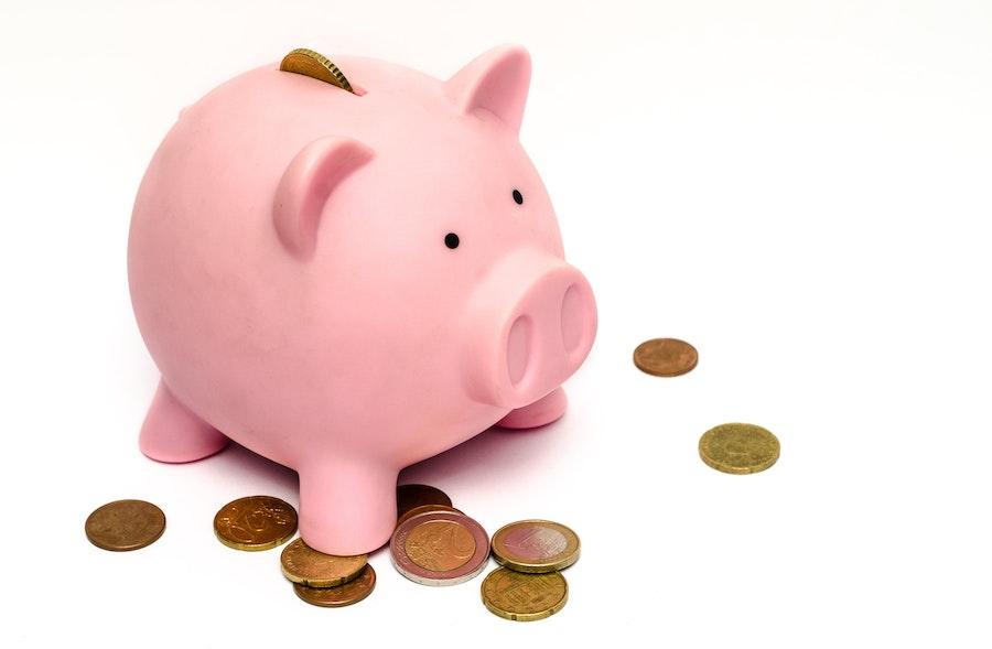 Sparschwein und Münzen liegen verteilt auf Tisch