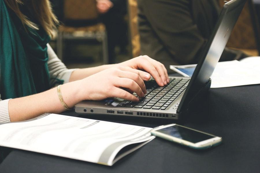 Frau tippend an Laptop